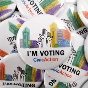 "A pile of buttons with the words ""I'm Voting"" and a colourful cityscape and raised hands on them."
