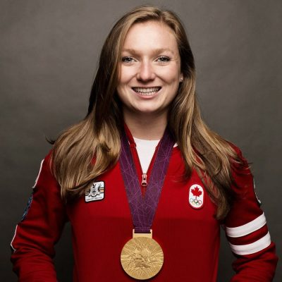 Rosie Maclennan smiles in an Olympic shirt that says, 'Canada'.